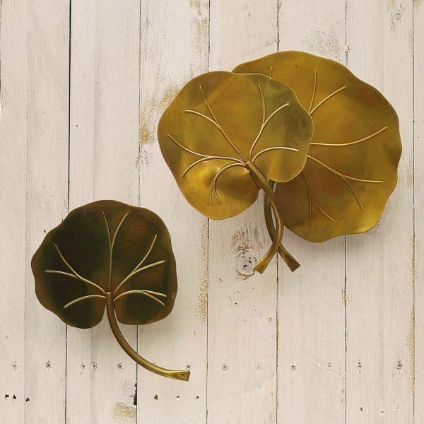 Belle paire d'appliques en laiton doré à la forme de feuilles de nénuphars datant des années 60. Une applique double feuille et une simple. Quelques petites piqures sans gravité sur les feuilles, accroche à l'arrière. Bon état général.