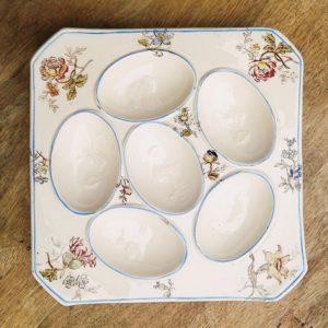 Assiette de présentation pour les oeufs, en faïence de Longchamp terre de fer. Un dessin en relief dans le fond de chaque emplacement pour les oeufs.
