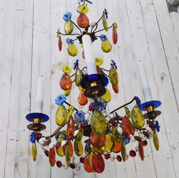 Lustre à pampilles colorées en verre de Murano datant des années 60-70. Structure en bronze doré à quatre feux de lumières. Lustre richement décoré de pampilles et guirlandes de couleurs, à la forme de gouttes à facette et de fleurs