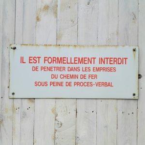 Plaque émaillée ancienne de signalisation pour la SNCF, formulant une interdiction de pénétrer dans les emprises du chemin de fer