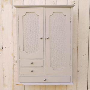 Petit meuble de rangement mural, en bois peint gris perle. Composé de deux portes et de trois tiroirs. Le décor des portes est composé d'une plaque de verre peinte à motifs, les boutons de poignée sont en métal brossé ( ils sont neufs). 2 attaches permettant de l'accrocher au mur si désiré.