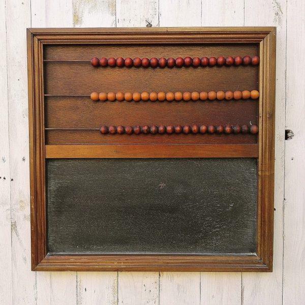 Boulier et tableau noir en bois, les boules sont en buis de trois couleurs différentes. Une boule est fendue, le tableau est usé. Trace d'usage.