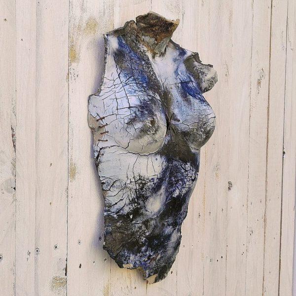 Sculpture contemporaine d'un buste de femme, en grès recouvert de grès porcelainique, avec effet de craquelures dans les tons de bleu-gris et effet de sutures en fils de cuivre. Un point d'accroche mural à l'arrière
