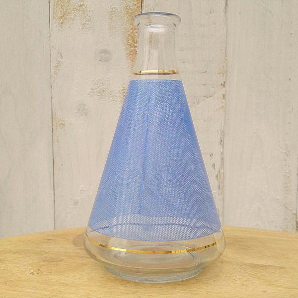 Carafe en verre à décor d'alvéoles de couleur bleue, avec un liseré doré sur le bas et au col de la carafe. Typique des années 50. Très bon état.
