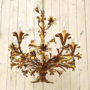 Lustre de la maison Baguès en métal doré à la feuille d'or, composé de cinq feux de lumières. Richement orné de multiples fleurs formant un bouquet maintenu dans sa partie basse par un lien à la forme de cordelette typique de cette maison.