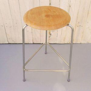 """Tabouret tripode modèle """"Dot"""" créé et dessiné par Arne Jacobsen, édité par Fritz Hansen. Assise en bois lamellé collé, piétement en métal brossé,daté de 1971. Traces d'usage et tâches de verni sur l'assise, petit décollement du placage à un endroit (visible photo). Traces d'oxydation sur le piétement."""