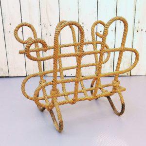 Porte revueAudoux Minet datant des années 50-60, piétement en fer gainé de cordage tressé. Trace d'humidité sur les pieds, rayures d'usage sur le plateau. Dans son jus Hauteur : 33 cm Largeur : 39 cm Profondeur : 24 cm