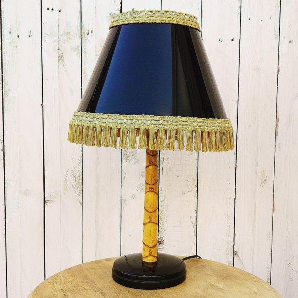Lampe à poser datant des années 50, pied bambou et abat jour laqué noir à frange doré. L'intérieur de l'abat jour est doré miroir créant une luminosité chaleureuse. Interrupteur en bakélite d'origine. Très bon état. Hauteur : 51 cm