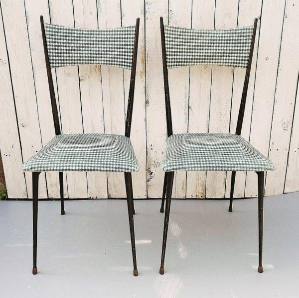 Paires de chaises datant des années 50-60, à damier ou pied de poule blanc et noir, dessinées par Colette Guéden pour primavera. Assise et dossier avec leur garniture d'origine en vinyle, structure tubulaire en acier laqué noir, bout des pieds en laiton. Assise et dossier défraîchis par l'usage, manque de peinture laquée noire sur les tubulures. Dans son jus Hauteur totale : 90 cm Hauteur assise : 45 cm Dimensions assises : 35 x 38 cm