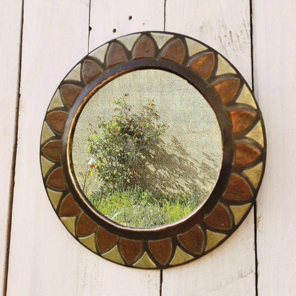 Miroir soleil ou fleur, contour en cuivre et laiton. Un point d'accroche à l'arrière. Petites tâches sur le miroir. Bon état Diamètre : 25,5 cm