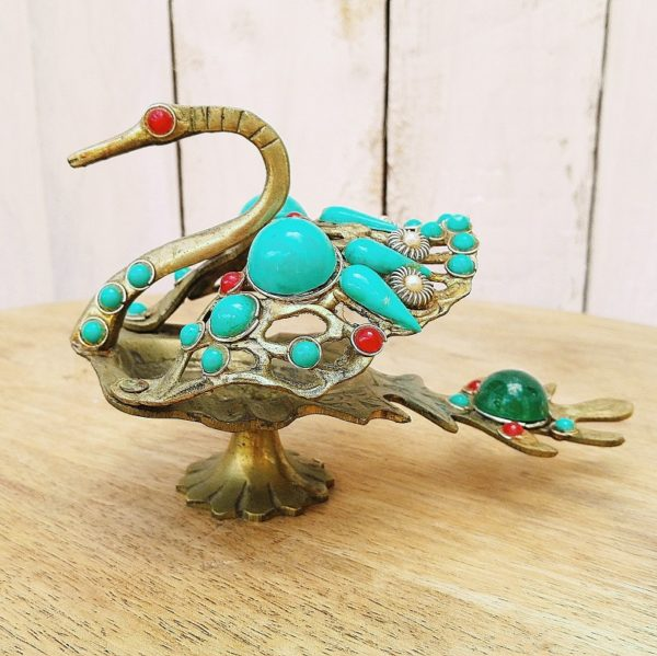 Oiseau fantastique en laiton et orné de perles couleur turquoise pouvant servir de baguier, les ailes se déploient. . Traces d'usages, manque une petite perle. Hauteur : 10,5 cm Longueur : 14 cm