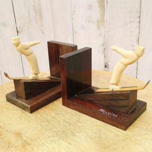 Serre livres art déco datant des années 40-50, représentant des skieurs en bakélite écrus. Souvenir de Morzine. Manque de verni à certains endroits du bois de support, les deux skieurs sont recollés au niveau des chevilles et l'un des skieur est craquelé, le bout ses skis est fendu. Dans leur jus. Hauteur avec skieur : 14 cm dimensions du socle : 15 x 9 cm