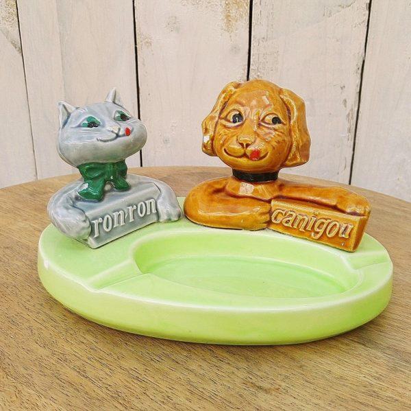 Cendrier publicitaire en céramique pour la marques canigou et ron-ron, pouvant servir de vide-poche. Petits éclats, sur le bord du cendrier, la truffe du chat et l'oreille du chat. Bon état général. Hauteur : 11 cm Longueur : 20 cm