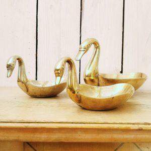 Vide poche ou baguier en forme de canard, en laiton doré, décoration vintage. Traces de piqûres sur l'intérieur des trois canards et sur l'extérieur. Une trace de vert de gris sur l'extérieur d'un petit canard. Dans leur jus Dimension du grand canard : 10,5 x 18 x 11 cm Dimension petit canard (2) : 6,5 x 13 x 8,5 cm