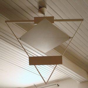Rare lustre, suspension datant des années 80, dessiné par Mario Botta en métal laqué blanc. Reflecteur inclinable de façon à modifier la luminosité. Un petit manque de peinture sur une pointe du triangle. Excellent état. Hauteur hors fil : 68 cm Largeur : 80 x 50 cm