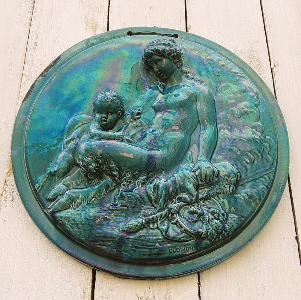 Médaillon tondo en céramique émaillée bleu canard représentant une faunesse jouant avec son enfant, d'après Clodion. SignéClodion en bas. Un manque d'émaillage d'origine sur la partie gauche, plusieurs petites egrenures sur le décor. Bon état général Diamètre : 29 cm