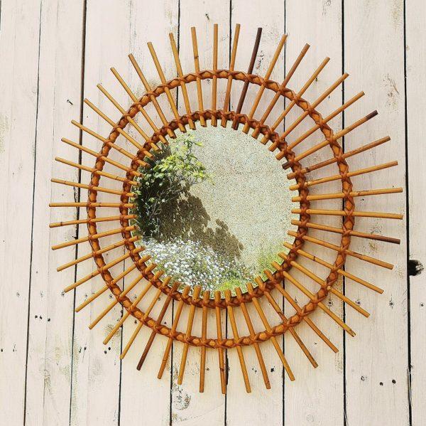 Miroir soleil en rotin, datant des années 60, pour une décoration bohème et tendance. Très bon état Diamètre : 61 cm Diamètre miroir : 31 cm