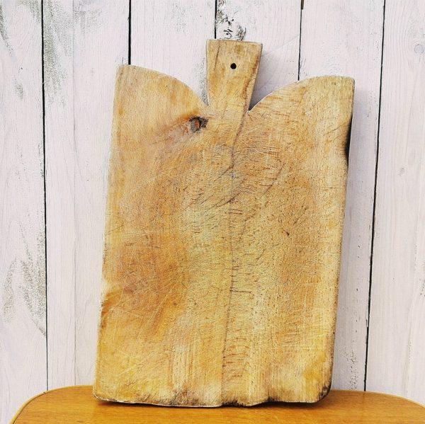 Ancienne planche à découper, billot de cuisine, en bois dur. Sa forme originale saura intégrer votre cuisine pour lui donner un charme certain. Rayure de couteaux sur les deux faces, bois noirci sur le bas de la planche. dans son jus. Dimensions : 40 x 26 cm