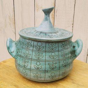 Pot couvert en céramique datant des années 50, à décor en retenue de fleurs. Créé par Jean de Lespinasse. Deux égrenures sur la prise du couvercle. Très bon état général. Hauteur avec couvercle : 23,5 cm Hauteur sans couvercle : 14 cm Diamètre : 26 cm