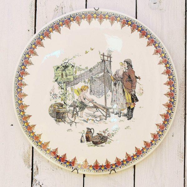 Rare grand médaillon décoratif en faience de Sarreguemines par Froment Richard, représentant une scène d'un cupidon en tonnelier devant un couple venant chercher du vin. Médaillon datant de 1875-1900. Signature et marque à l'arrière Faience craquelée . Deux micros égrenures sans incidence. Très bon état Diamètre : 31 cm