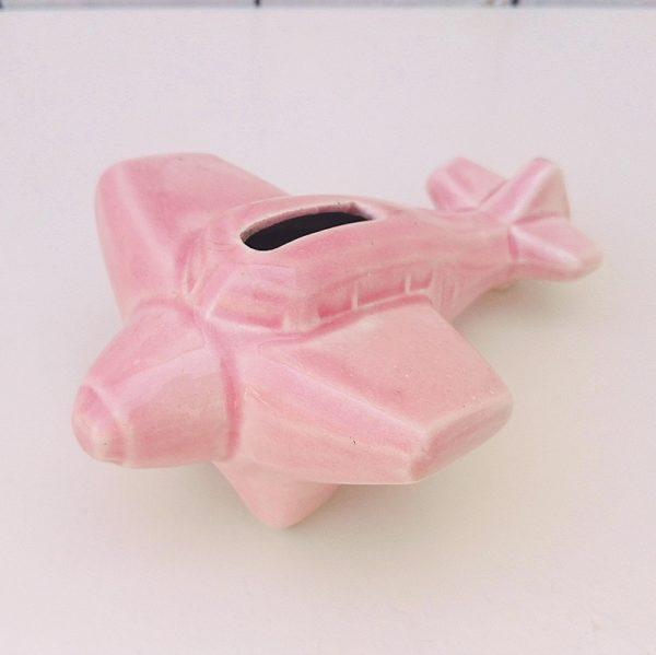 Tirelire a casser en forme d'avion en céramique rose de Onnaing, numéro 953. Excellent état. Dimensions : 15 x 10,5 cm