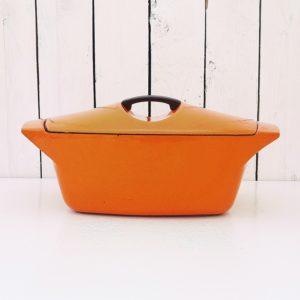 Cocotte en fonte émaillée de couleur orange datant des années 50, dessinée par Raymond Loewy pour Le Creuset. Cocotte de contenance 3,5 litre. Poignée du couvercle et de la cocotte en fonte permettant de la mettre au four. Un petit éclat sur le contour du couvercle sans gravité. Très bon état. Longueur avec poignées : 32 cm Longueur sans poignées : 26 cm Largeur : 20,5 cm Hauteur : 10 cm