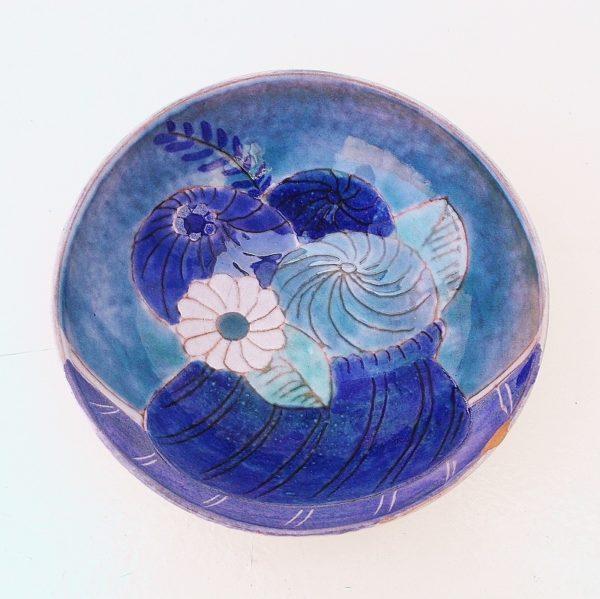 Coupelle aux fleurs dans un camaïeu de bleu en céramique datant des années 70. Signé Cloutier. Un choc sur le col (voir photo). Bon état général. Hauteur : 5 cm Diamètre : 14 cm