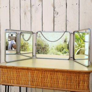 Grand miroir triptyque de barbier datant des années 50 à décor de fleurs quand il est fermé. La bordure est en métal chromé, une chaînette permet de le suspendre. Possède un fermoir. Les miroirs sont en bon état. Traces de scotch sur le décor floral, et traces d'usage. bon état général. Dimensions d'un miroir : 28 x 21,5 cm Dimensions déployé : 88 x 23,5 cm