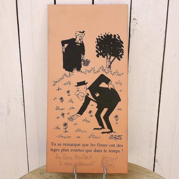Parefeuille de Provence en terre cuite, illustré et dédicacé par le dessinateur humoristique Jacques Faizant. Numéroté exemplaire 60/200. Excellent état. Dimensions : 41,5 x 20 cm