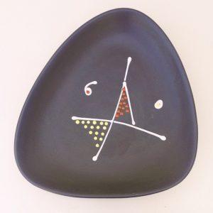 Grand plat en céramique à décor très graphique datant des années 50. Signé André Baud à Vallauris. Le décor est en relief émaillé. Un petit éclat sur un coin, et un saut d'émail qui a été recollé. Très bon état. Dimensions : 38 x 33 cm au plus large.