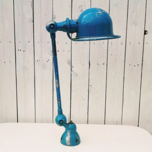 Lampe industrielle d'atelier dessinée par Jean Louis Domecq pour la marque Jielde datant des années 50. Un bras articulé, et possède sa base pour la fixer ainsi que sa plaque. De couleur bleue et réflecteur blanc émaillé. Des chocs sur le globe, peinture enlevée à plusieurs endroits, traces d'usage. Dans son jus. Longueur : 76 cm