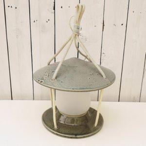 Lampe en céramique de forme tempête à suspendre. Chapeau et socle en céramique émaillée maintenu entre eux avec du cordage, globe en verre poli. Très bon état. Hauteur totale : 41 cm