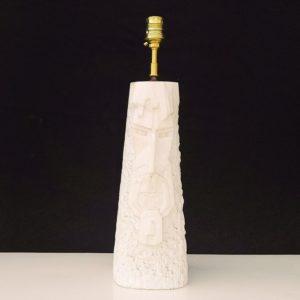 Lampe en marbre blanc sculptée d'un visage ethnique sur l'avant. Effet granité sur le pied. Lampe datant des années 70-80. Trace de corrosion autour de la rondelle supportant la douille. Quelques taches sur le pied. Bon état général. Hauteur avec douille : 40 cm