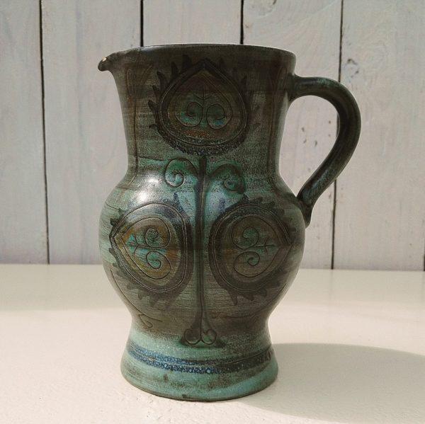 Pichet en céramique à décor de fleurs stylisées, signé Jean de Lespinasse sur le dessous. Une micro égrenure sur le bec, effet craquelé à l'intérieur. Très bon état. Hauteur : 18 cm