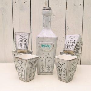 Service à whisky en céramique signé Vallauris, comprenant une bouteille et son bouchon et six gobelets. Décor contemporain scarifié sur la bouteille et les gobelets. Excellent état. Hauteur bouteille : 29,5 cm Hauteur gobelets : 10 cm