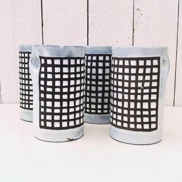 Quatre mugs à anse pincée en céramique par Roger Capron à Vallauris. Décor de damier, typique du travail de l'artiste. Egrenures et petits éclat sur les cols et bases de chaque mug, et un fêle sur un seul mug. Dans leur jus Hauteur : 13 cm Diamètre : 7,5 cm