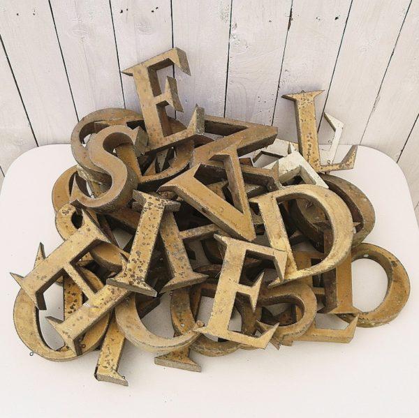Quarante lettres d'enseigne en métal doré dont trois blanches datant des années 50-60. elles possèdent toutes leurs deux point d'accroches. Traces de corrosion, et quelques enfoncement de certaines lettres. Le lot comprend : 1-C, 2-D, 7-E, 2-H, 5-I, 2-L, 2-N, 7-O, 2-Q, 2-R, 4-S, 3-T, 1-V Dans leur jus. Hauteur : 15 cm Largeur : 13 cm Profondeur : 3 cm