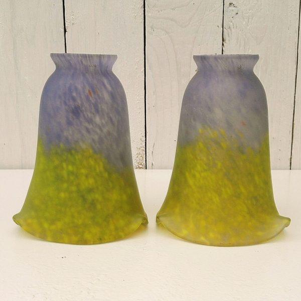 Paire de tulipes en pâte de verre, datant des années 20-30, époque art déco. De couleur vert-jaune sur la base et violet-bleu sur le haut. Micros éclats au niveau de l'emplacement de la griffe de suspension. Quelques rayures d'usage. Très bon état. Hauteur : 15 cm