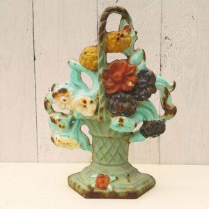 Ancienne butée ou arrêt de porte en fonte polychrome, à décor de panier fleuri. Dans les tons de bleu turquoise pour le panier, et de fleurs blanches, rouges,violettes et jaunes Traces de corrosion sur le devant et l'arrière. Dans son jus. Dimensions : 22,5 x 13 cm
