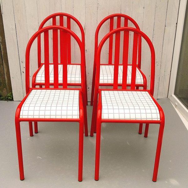 Série de quatre chaises Robert Mallet Stevens, en tubulure laquée rouge, assise thermoformée à carreaux . Chaises empilables permettant un gain de place. Typique des années 80. Traces d'usages sur les assises sans gravité, petits sauts de peintures au niveau de l'empilement. Hauteur totale : 84 cm Hauteur assise : 45 cm Largeur : 39 cm Profondeur : 43 cm