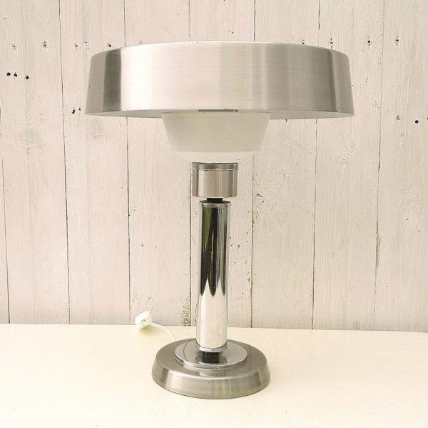Lampe datant des années 70 au design dans le style art déco. Pied et réflecteur en alu brossé, tube central chromé. Intérieur du réflecteur laqué blanc. Décollement et manques de chrome sur le disque de serrage du réflecteur, interrupteur neuf. Bon état général. Hauteur : 39 cm Diamètre réflecteur : 29,5 cm