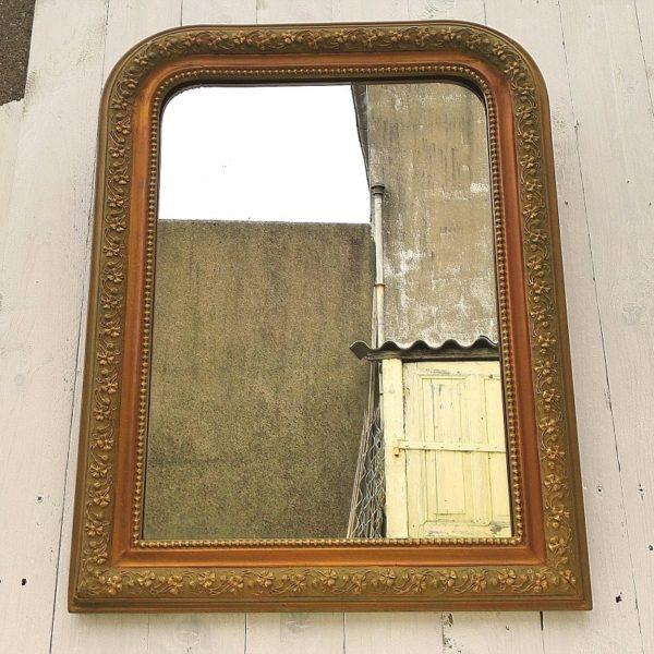 Miroir style Louis Philippe en bois stuqué doré, à bordure perlée et décor de fleurs. Petites éclats de stuc sans gravité et un féle sur un des arrondis. Très bon état général. Dimensions : 67 x 51 cm