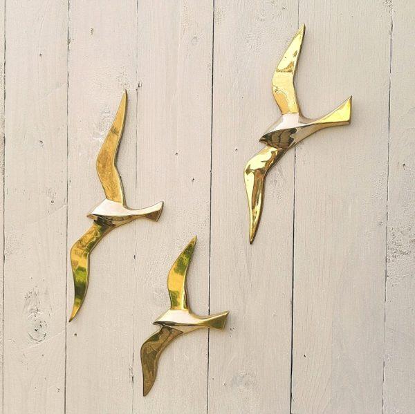 Volée de trois mouettes en laiton doré, trois tailles différentes. Elles sauront habiller votre mur. Quelques petites tâche de corrosion, traces de rayures d'usage sans gravité. Une tâche sur aile d'une mouette. Bon état général. Envergures : 30 cm, 24,5 cm et 21 cm