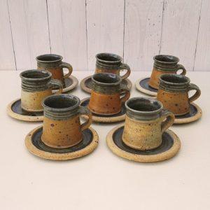 Lot de huit tasses à café avec leurs sous tasses, en grès pyrité émaillé bleu sur l'intérieur, datant des années 60, par Pierre Digan à La borne. Un fèle sur le fond de deux tasses n'affectant pas leur étanchéité, un éclat au col d'une tasse, anse cassée recollée ainsi qu'un fèle et éclats sur une autre tasse, quatre tasses en très bon état. Les sous tasses sont en bon état, quelques défauts de cuisson sur l'émail sans gravité. Les sous tasses sont toutes différentes. Bon état général. Hauteur tasse : 6,5 cm Diamètre tasse : 5,5 cm Diamètre sous tasse : 11 cm