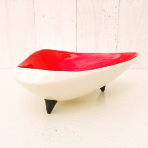 Ancien vide poche tripode en céramique, émaillé rouge sur l'intérieur, blanc sur l'extérieur et noir pour les pieds. Datant des années 50. Une marque sur le dessous. Petits éclats sur le pourtour, usure des trois pieds. Bon état général. Hauteur : 6,5 cm Longueur : 24 cm Largeur : 14,5 cm