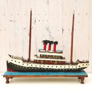 Ancienne maquette d'un paquebot cargo en bois peint à la main. Réalisé probablement par un des marins qui naviguait sur ce paquebot. Les marins avaient pour habitude de reproduire à l'identique les bateaux sur lesquels ils naviguaient se servant de ce qu'ils avaient sous la mains, tel que de la laine pour reproduire la fumée des cheminées par exemple. Maquette d'art populaire de conception naïve posée sur un socle quadripode en bois représentant la mer. Des manques sur les passerelles, un éclat à la proue du bateau, quelques chocs et rayures d'usage. Doit probablement manquer les voiles. Dans son jus. Hauteur : 46 cm Longueur : 53 cm Largeur : 12,5 cm