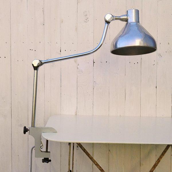 Lampe Jumo modèle GS1, en métal chromé et abat jour en aluminium. Pied étau, bras et abat jour réglable. Interrupteur à l'arrière de l'abat jour à changer car coincé en position allumé. Traces et rayures d'usage. Bon état général Longueur max : 90 cm