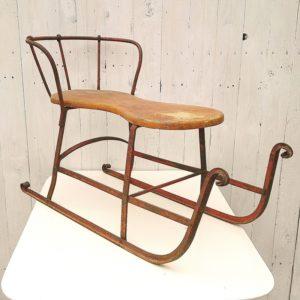 Ancienne luge traîneau datant des années 20, structure en fer peint en rouge, assise en bois en clair. Corrosion sur la structure et le dossier, usure du vernis de l'assise. Bon état. Hauteur avec dossier : 50 cm Hauteur assise : 33 cm Longueur : 78 cm Largeur 27,5 cm