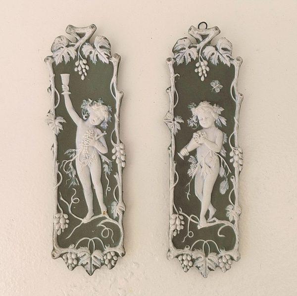 Paire de plaques décoratives en biscuit, de la manufacture anglaise Wedgwood. Représentant des enfants à l'antique sous la vigne. Un petit manque sur une feuille de vigne en haut à gauche de la plaque à l'enfant remplissant son calice. Bon état général. dimensions : 18 x 5 cm