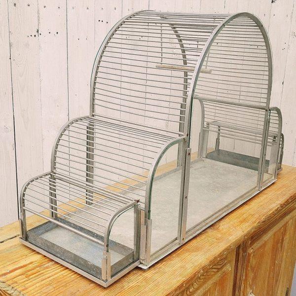 Grande cage à oiseaux art déco, structure en aluminium et plaques de verre. Sa forme arrondie lui confère un certain charme. Quelques traces d'usage sans gravité. Très bon état. Hauteur : 52 cm Longueur : 90 cm Profondeur : 29 cm